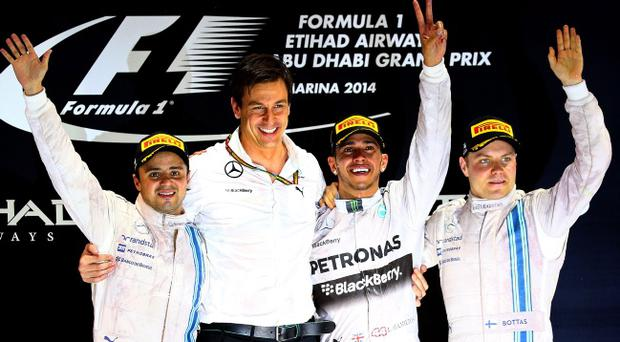 Top of the world: Toto Wolff and Lewis Hamilton celebrate T the title at Abu Dhabi