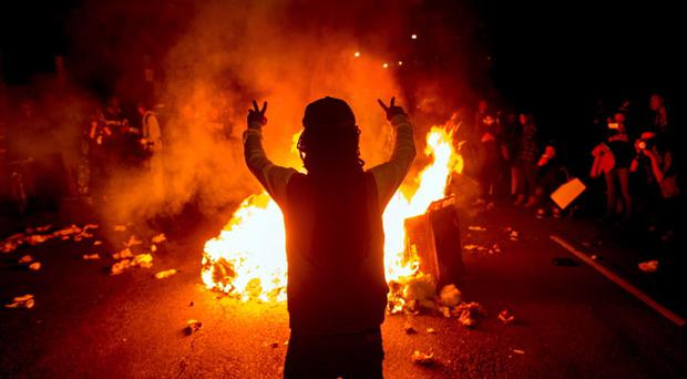 Demonstrators protest in Oakland, Calif., on Monday, Nov. 24, 2014, after the announcement of the grand jury decision not to indict Ferguson police officer Darren Wilson in the fatal shooting of Michael Brown, an unarmed 18-year-old. (AP Photo/Noah Berger)