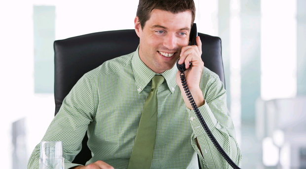 Businessman sitting in office with personal organizer on telepho