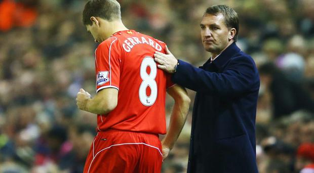 Steven Gerrard of Liverpool prepares to come onto the pitch as a substitute alongside Brendan Rodgers manager of Liverpool during the Barclays Premier League match between Liverpool and Stoke City at Anfield on November 29.