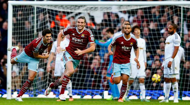 Andy Carroll of West Ham celebrates scoring their second goal with James Tomkins of West Ham during the Barclays Premier League match between West Ham United and Swansea City at Boleyn Ground. Photo by Julian Finney/Getty Images.