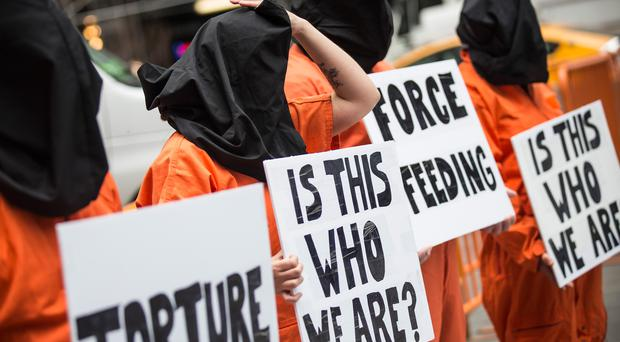 NEW YORK, NY - MAY 23: Protestors demand the closure of the Guantanamo Bay detention center, used by U.S. military forces to hold people indefinitely, in Times Square on May 23, 2014 in New York City. Organizers of the protest claimed the gathering was in coordination with protests happening in 40 other cities. (Photo by Andrew Burton/Getty Images)