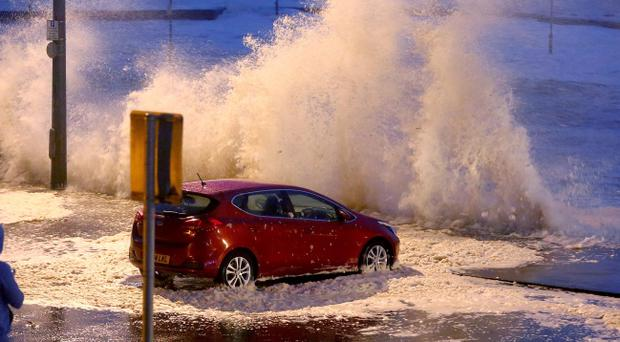 A car on the peer of Portstewart surrounded by water