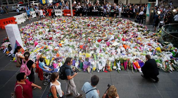 SYDNEY, AUSTRALIA - DECEMBER 16: A man places flowers as a mark of respect for the victims of Martin Place siege on December 16, 2014 in Sydney, Australia. (Photo by Daniel Munoz/Getty Images)