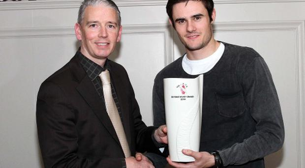 Winner: John Martin, Chairman of the Ulster GAA Writers Association, presents the monthly Merit Award to Derry star Chrissy McKaigue