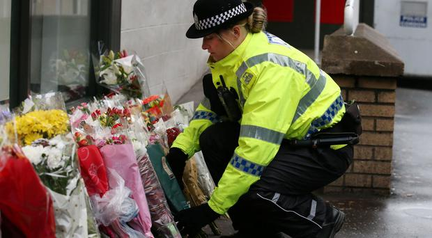 A police officer places flowers close to the scene in George Square, Glasgow, where a bin lorry crashed into a group of pedestrians. Pic Andrew Milligan/PA Wire