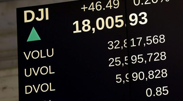 An electronic display shows the Dow Jones Industrial Average above 18,000 on the floor of the New York Stock Exchange in New York, Tuesday, Dec. 23, 2014. U.S. stocks pushed further into record territory on Tuesday as the Dow Jones industrial average crossed past the 18,000-point mark for the first time. (AP Photo/Seth Wenig)