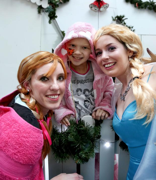 Christmas cheer: Molly Taylor with panto stars Anna and Elsa from Frozen at the Royal Victoria Children's Hospital