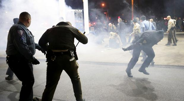 Police try to control a crowd Wednesday, Dec. 24, 2014, on the lot of a gas station following a shooting Tuesday in Berkele. Pic. AP Photo/St. Louis Post-Dispatch, David Carson