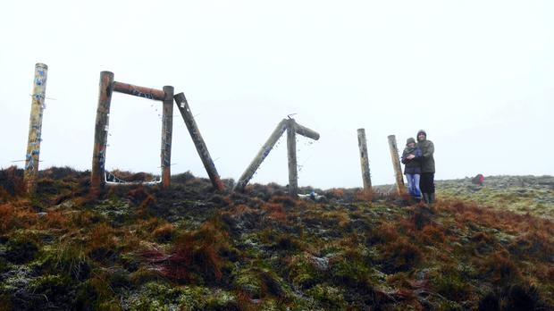 John Moore and Diane Alexander on Slemish mountain with his proposal spelt out in wooden letters