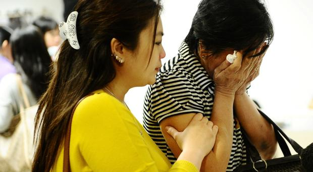 Relatives of missing Air Asia QZ8501 passengers cry at the crisis centre of Juanda International Airport Surabaya on December 28, 2014 (Photo by Robertus Pudyanto/Getty Images)