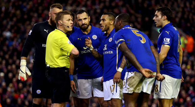 Standing firm: Leicester City players surround referee Mike Jones after his penalty decision