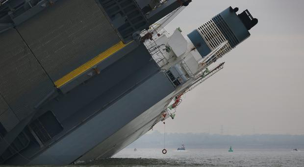 A lone life ring hangs by a rope from the listing hull of the stricken vessel 'Hoegh Osaka' after it ran aground on a sand bank in the Solent on January 4, 2015 in Cowes, England. The cargo ship ran aground on Bramble Bank after leaving Southampton bound for Germany. All 25 crew members were rescued overnight. (Photo by Peter Macdiarmid/Getty Images)