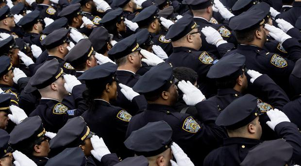 Thousands of New York city police officers turned their backs on Mayor Bill de Blasio as he spoke at the funeral of an officer shot dead with his partner