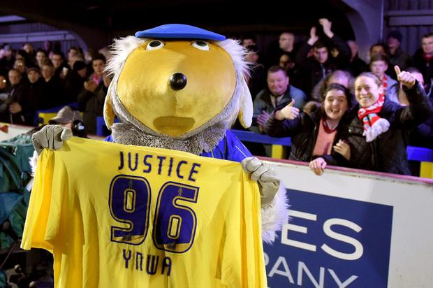 Haydon the Womble the Wimbledon mascot holds up a shirt in memory of the victims of the Hillsborough disaster (Photo by Michael Regan/Getty Images)