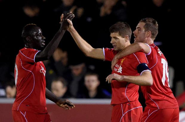 Steven Gerrard of Liverpool is congratulated by teammates Mamadou Sakho and Jordan Henderson after scoring his team's second goal from a free kick during the FA Cup Third Round match between AFC Wimbledon and Liverpool at The Cherry Red Records Stadium on January 5, 2015 in Kingston upon Thames, England. (Photo by Michael Regan/Getty Images)