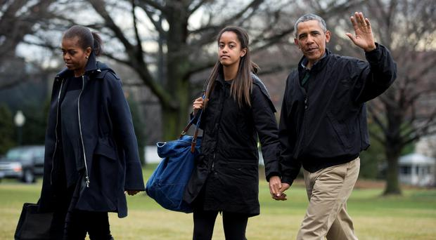 President Barack Obama with first lady Michelle Obama and daughter Malia as they arrive at the White House from a family vacation in Hawaii. (AP Photo/Manuel Balce Ceneta)