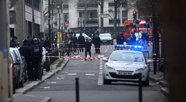 Ambulances and police officers gather in front of the offices of the French satirical newspaper Charlie Hebdo on January 7, 2015 in Paris, France. Armed gunmen stormed the offices leaving twelve dead, including two police officers, according to French officials. (Photo by Antoine Antoniol/Getty Images)