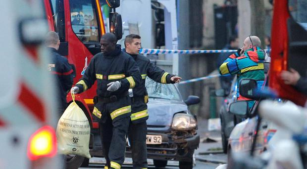 Rescue workers remove items after a shooting in Montrouge, outside Paris, Thursday, Jan. 8, 2015. Two people were shot and gravely wounded at the southern edge of Paris, including a police officer, raising tensions a day after masked gunmen stormed the offices of a satirical newspaper and killed 12 people. (AP Photo/Christophe Ena)