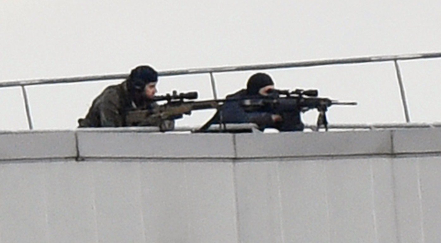 Police marksmen take up a position on a roof in Dammartin-en-Goele, north-east of Paris, where two brothers suspected of slaughtering 12 people in an Islamist attack on French satirical newspaper Charlie Hebdo held one person hostage as police cornered the gunmen, on January 9, 2015