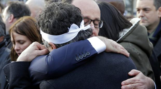 French President Francois Hollande (R) comforts French columnist for Charlie Hebdo Dr Patrick Pelloux as they attend the solidarity march (Marche Republicaine) in the streets of Paris. AFP / PHILIPPE WOJAZER / Getty Images.