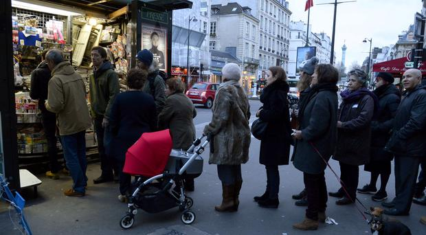 Parisians queue at a newspaper kiosk to get their copies of the latest edition of Charlie Hebdo