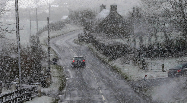 Motorists make their way through snowfall in Gortin near Omagh, as many parts of the UK were on snow alert with wintry showers threatening to disrupt travel. Niall Carson/PA Wire.