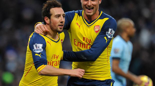 Breakthrough: Santi Cazorla is congratulated by Olivier Giroud after firing Arsenal in front at the Etihad Stadium