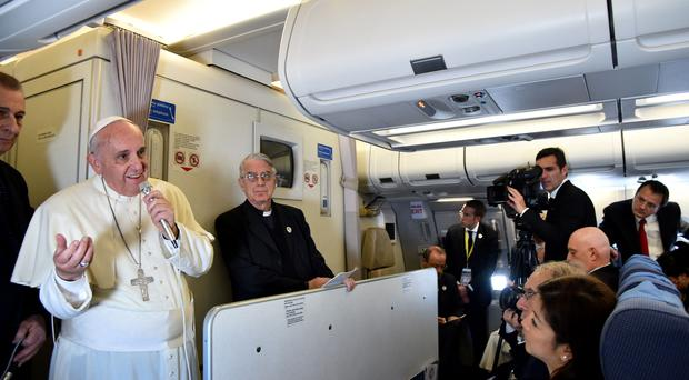 Pope Francis addresses journalists on a plane during his trip back to Rome following his successful visit to the Philippines and Sri Lanka where he was seeking to promote the Catholic Church in one of its most important growth regions