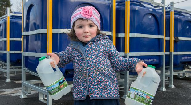 Dara Campbell (3) from Claudy helps to get water from tanks in the village centre yesterday as the industrial dispute over pensions at NI Water continues