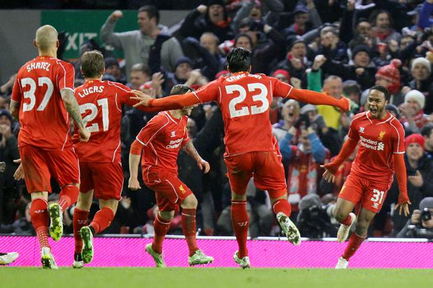 Liverpool's Raheem Sterling (right) celebrates scoring his sides first goal of the game during the Capital One Cup Semi Final, First leg at Anfield, Liverpool.