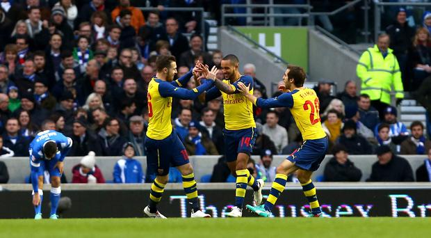Arsenal's Theo Walcott (centre) celebrates scoring his side's first goal alongside teammates Aaron Ramsey (left) and Mathieu Flamini (right) during the FA Cup Fourth Round match at the AMEX Stadium, Brighton. Gareth Fuller/PA Wire.
