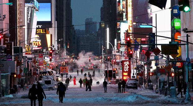 NEW YORK, NY - JANUARY 27: Pedestrians walk through Times Square on the morning of January 27, 2015 in New York City. New York, and much of the Northeast, was hit with heavy overnight snow from Winter Storm Juno. (Photo by Alex Trautwig/Getty Images)