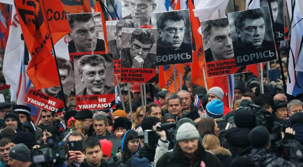 People march in memory of opposition leader Boris Nemtsov, who was gunned down on Friday, Feb. 27, 2015, with portraits of him and words read ' he died for the future of Russia, heroes never die!', near the Kremlin in Moscow, Russia, Sunday, March 1, 2015. (AP Photo/Dmitry Lovetsky)