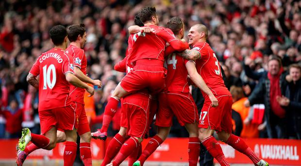Liverpool's Jordan Henderson (second right) celebrates scoring his side's first goal of the game with teammates during the Barclays Premier League match at Anfield, Liverpool. Lynne Cameron/PA Wire.
