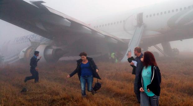 Passengers walk away from a Turkish Airlines plane after it skidded off the runway while landing at Kathmandu airport in the Nepalese capital Kathmandu on March 4, 2015. Aviation officials said no one on board was injured, although one witness described how terrified passengers leapt from their seats as the cabin filled with smoke after the plane skidded to a halt. AFP PHOTO / Dikesh MalhotraDikesh Malhotra/AFP/Getty Images