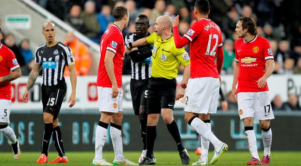 Referee Anthony Taylor separates Manchester United's Jonny Evans and Newcastle United's Papiss Demba Cisse