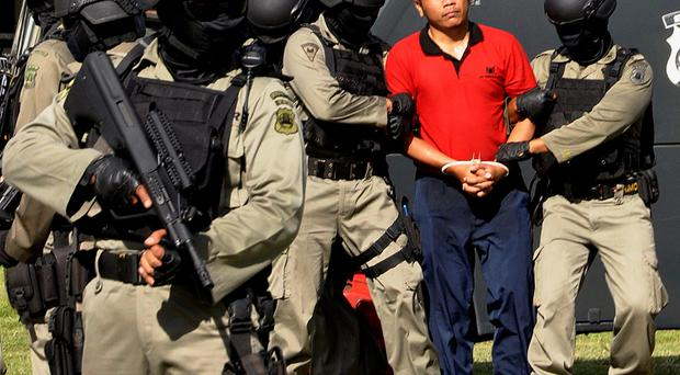 Indonesian police commandos secure a 'mock prisoner' during a simulation exercise in Danpasar on February 27, 2015, in preparation for the transfer of two Australian drug smugglers on death row.