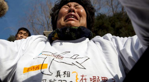 Liu Guiqiu, whose son was on board Malaysia Airlines Flight 370 that went missing, cries as she protests near the Malaysian Embassy in Beijing on the one year anniversary of the plane's disappearance, Sunday, March 8, 2015. (AP Photo/Ng Han Guan)
