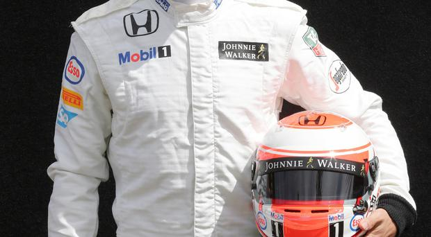 McLaren driver Jenson Button of Britain poses for a picture during a driver photo session ahead of the Australian Formula One Grand Prix at Albert Park in Melbourne, Australia, Thursday, March 12, 2015. (AP Photo/Rob Griffith)