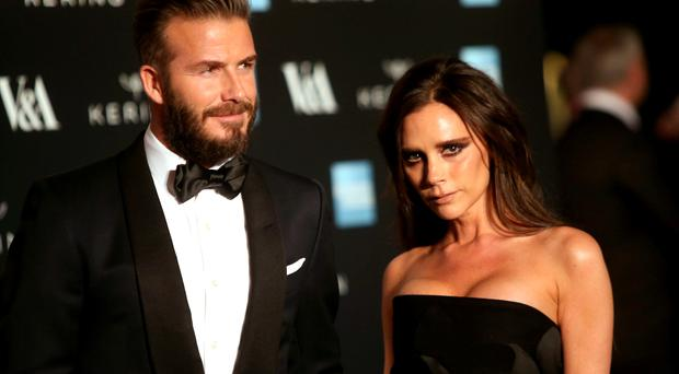 Former soccer player David Beckham and his wife, designer Victoria Beckham pose for photographers upon arrival at the Alexander McQueen Savage Beauty Gala exhibition