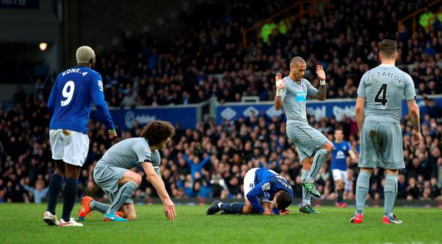 Everton's Aaron Lennon lays injured on the floor after a two footed tackle from Newcastle United's Fabricio Coloccini (second from left) during the Barclays Premier League match at Goodison Park, Liverpool. Lynne Cameron/PA Wire.