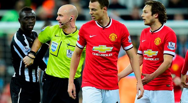 Manchester United player Jonny Evans (c) and Papiss Cisse of Newcastle have words during the Barclays Premier League match between Newcastle United and Manchester United at St James' Park on March 4, 2015