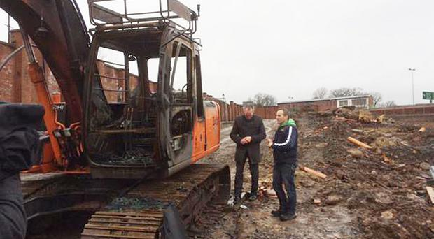 Sinn Fein MLA Gerry Kelly and Cllr JJ Magee next to a burnt out digger at a North Queen Street building site.