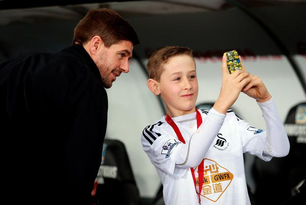 A young Swansea fan takes a selfie with Liverpool's Steven Gerrard as he arrives at the stadium for the Barclays Premier League match at the Liberty Stadium, Swansea