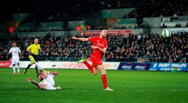 Liverpool's Jordan Henderson scores their first goal during the Barclays Premier League match at the Liberty Stadium, Swansea. PRESS ASSOCIATION Photo. Picture date: Monday March 16, 2015. See PA story SOCCER Swansea. Photo credit should read: David Davies/PA Wire. RESTRICTIONS: Editorial use only. Maximum 45 images during a match. No video emulation or promotion as 'live'. No use in games, competitions, merchandise, betting or single club/player services. No use with unofficial audio, video, data, fixtures or club/league logos.