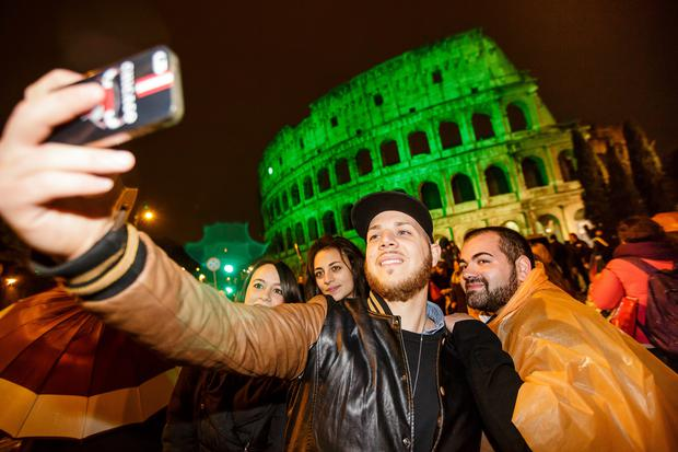 People in Rome taking selfies in front of the 'greened' Colosseum.