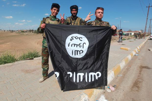 Iraqi Sunni and Shiite fighters pose for a photo with an Islamic State (IS) group flag in the Al-Alam town, northeast of the multi-ethnic Iraqi city of Tikrit, on March 17, 2015 after recapturing the town from IS fighters earlier in the month. AFP/Getty Images