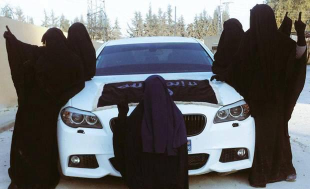 Women pose with a BMW M5 car. The reality of life under Isis is brutal for both fighters and civilians