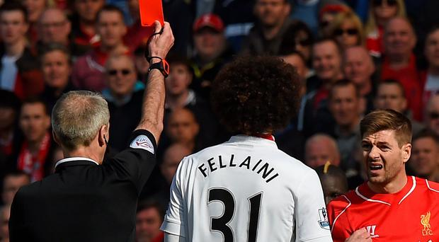 Liverpool's English midfielder Steven Gerrard is shown a red card by referee Martin Atkinson
